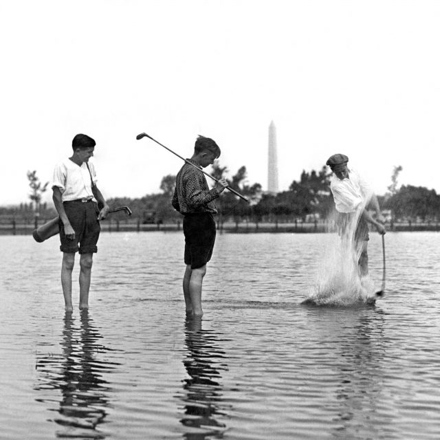 These early morning patrons of the Municipal golf course found a number of new water hazards from the six inches of rain the night before, Washington DC , August 13, 1928. These players refused to be daunted by the miniature lake and are playing their shots where they sank. Photo by Underwood & Underwood/Underwood Archives/Getty Images