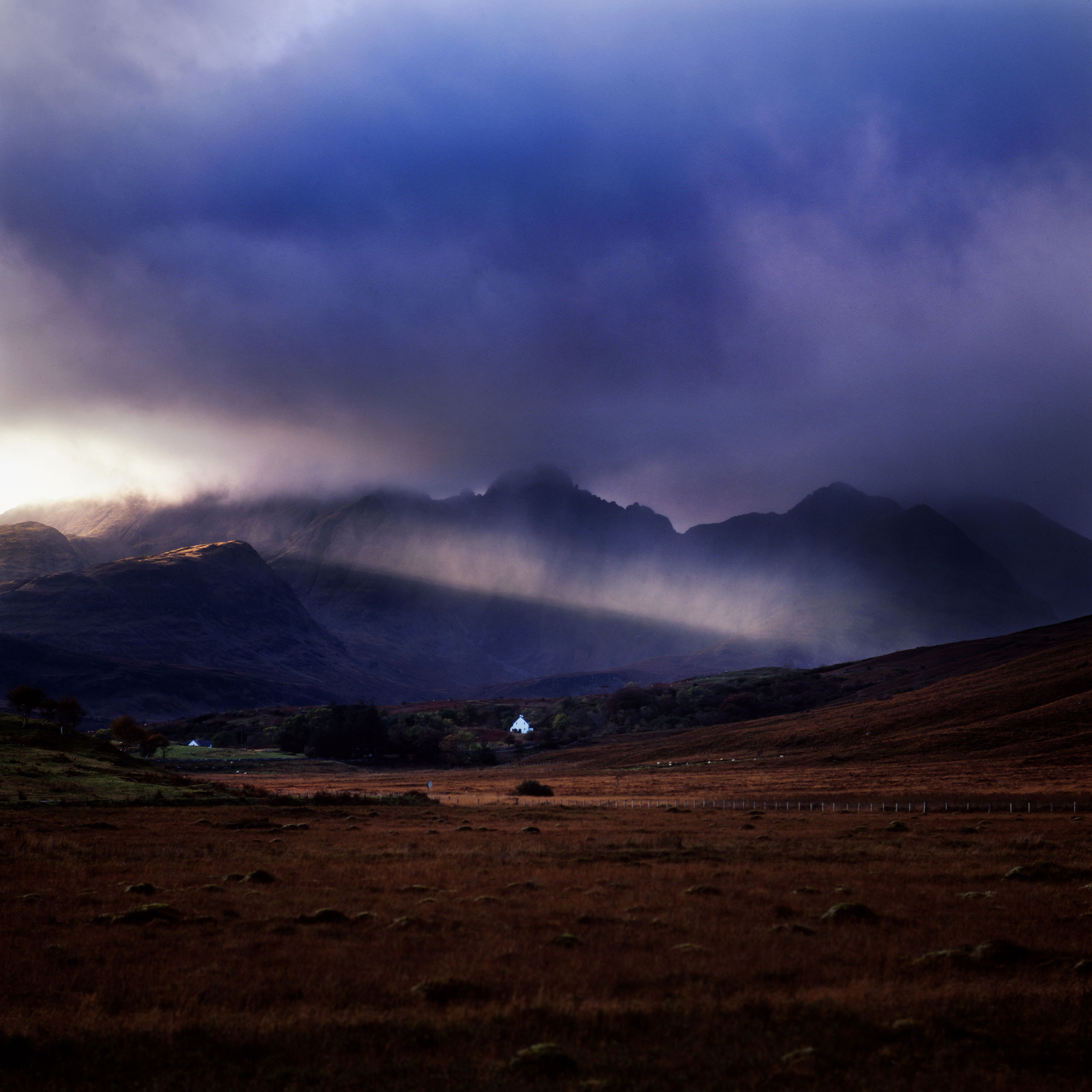 A lone house stands below Bla Behinn. Photo by Kieran Dodds