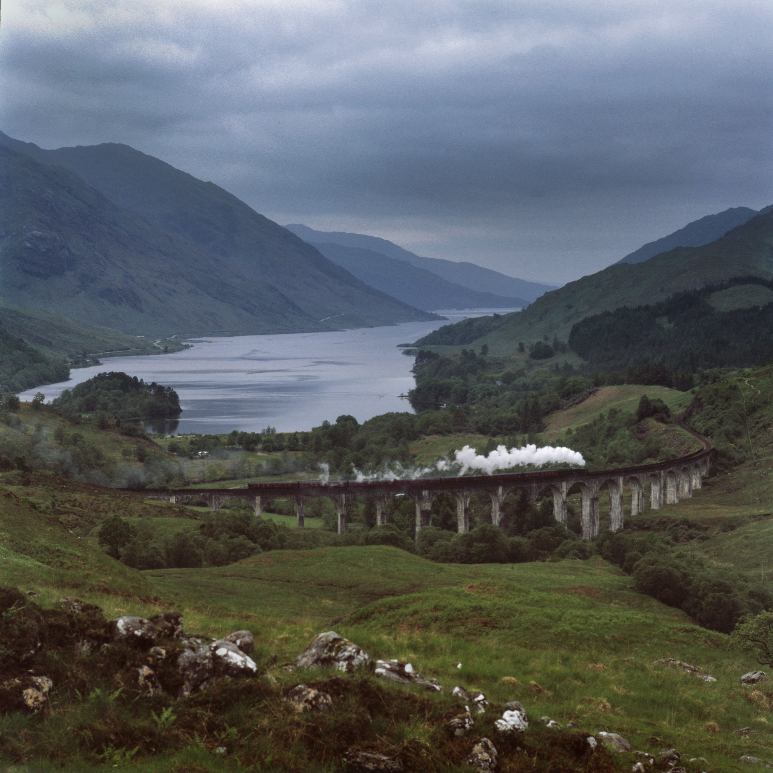The Jacobite Express train crosses the Glenfinnan viaduct above Loch Shiel where Bonnie Prince Charlie raised the Jacobite standard to start his rebellion which ended in defeat at Culloden in 1745. The loss brought about the dismantling of the highland clan system and rebranding by poets and writers of the Scottish identity to deepen a sense of solidarity and Britishness. Today the site is more famous for its role carrying the Hogwart's Express in the Harry Potter films written by Scot J.K.Rowling adding another chapter to the land's rich narrative. Photo by Kieran Dodds.