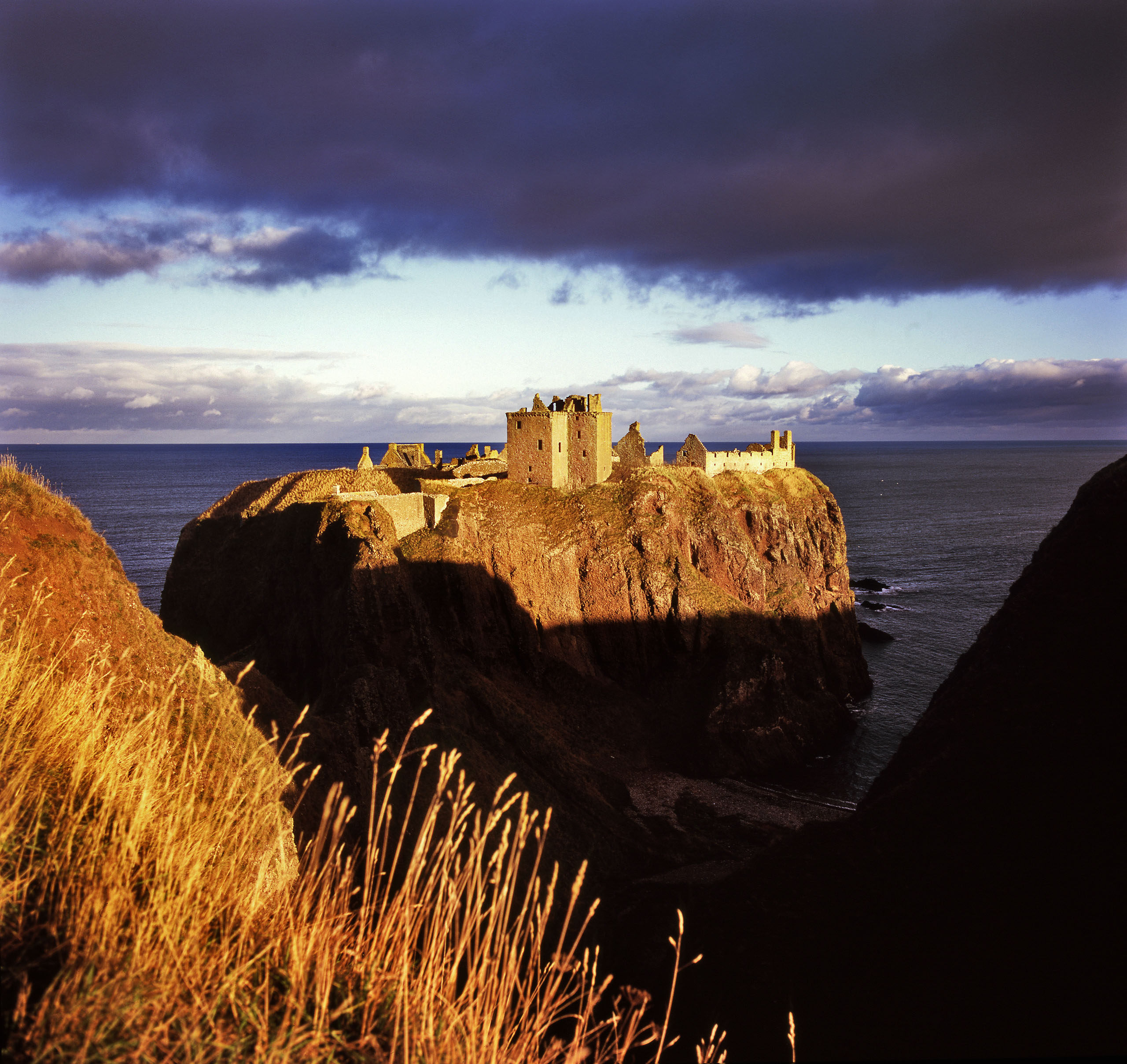 Medieval fortress Dunottar castle was home to one of the most powerful families in Scotland. The castle lies isolated off the coast near Stonehaven, Aberdeenshire where over centuries it has protected the likes of William Wallace, Mary Queen of Scots and countless tourists. The site was occupied since the Picts (this land's original settlers) from 5000BC-700AD (Dun is gaelic word for hill fort). In the 5th century the site was used as a Christian church by St Ninian who brought Christianity to the Picts. The castle is owned by Historic Scotland, a charity in the wider heritage sector who own 2.5% of Scottish land. Photo by Kieran Dodds.
