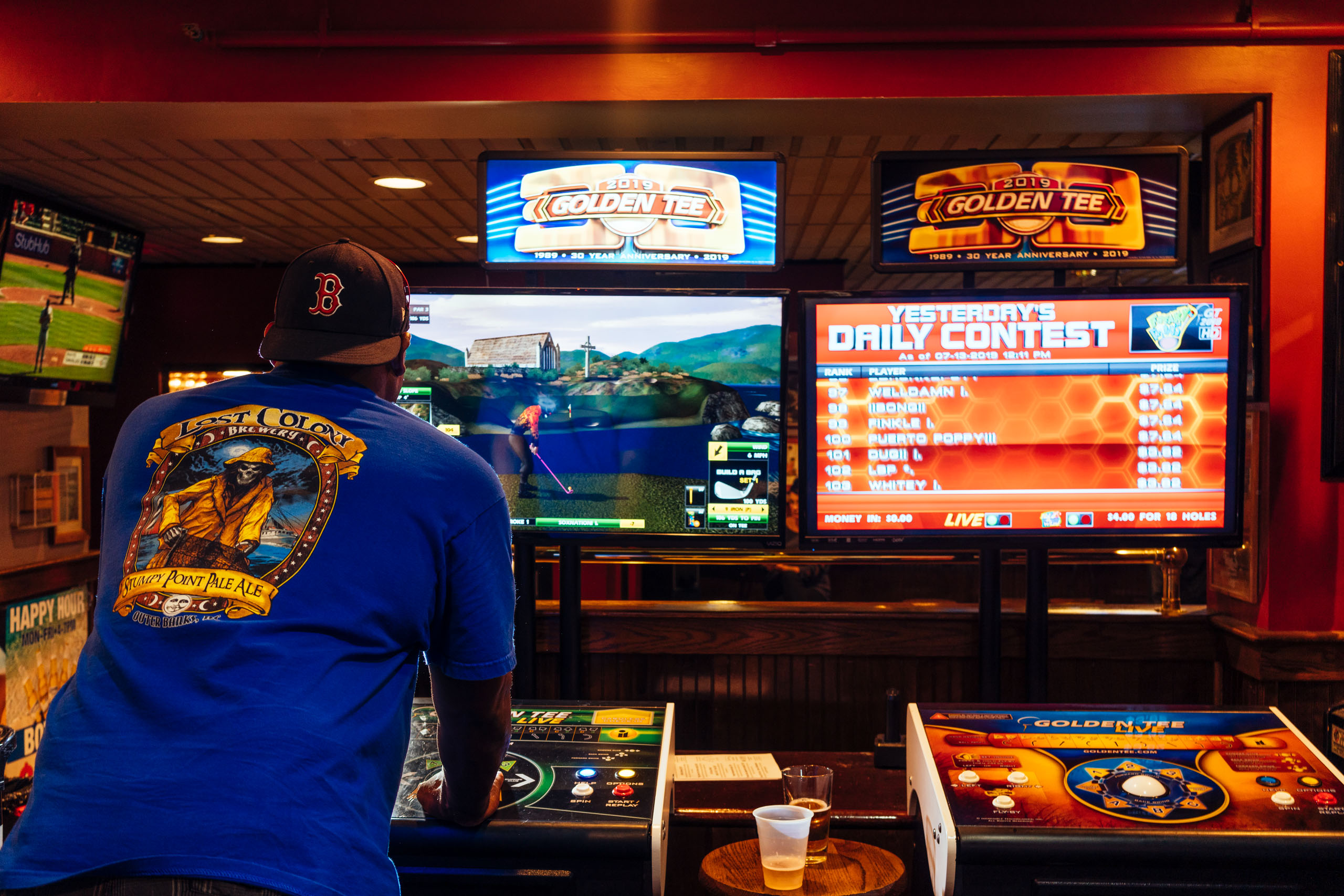 Players play the game Golden Tee, Photo by Lexey Swall