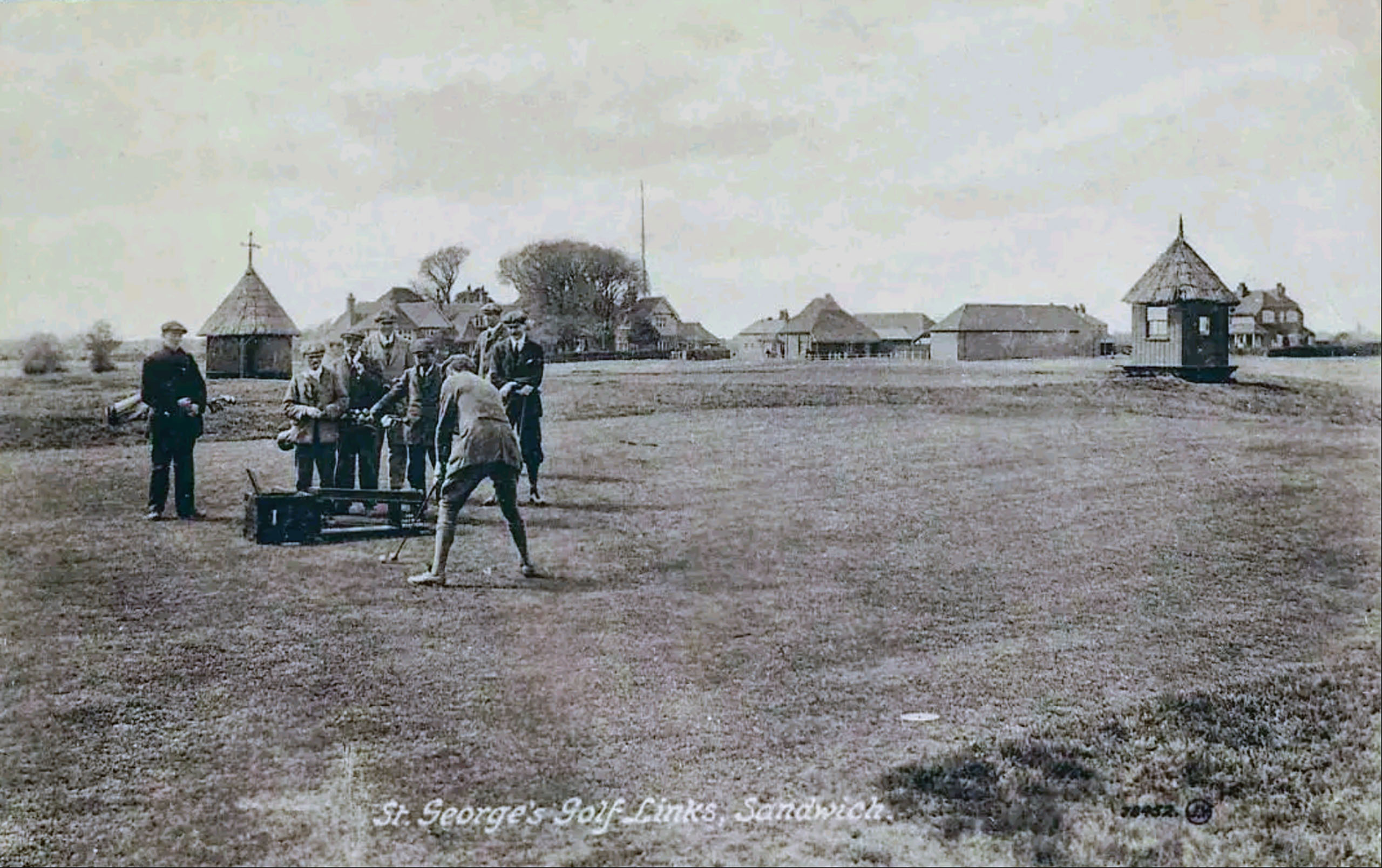 A 1907 postcard showcases players teeing off at the first, with thatched shelters and Royal St. George's original clubhouse in the background.