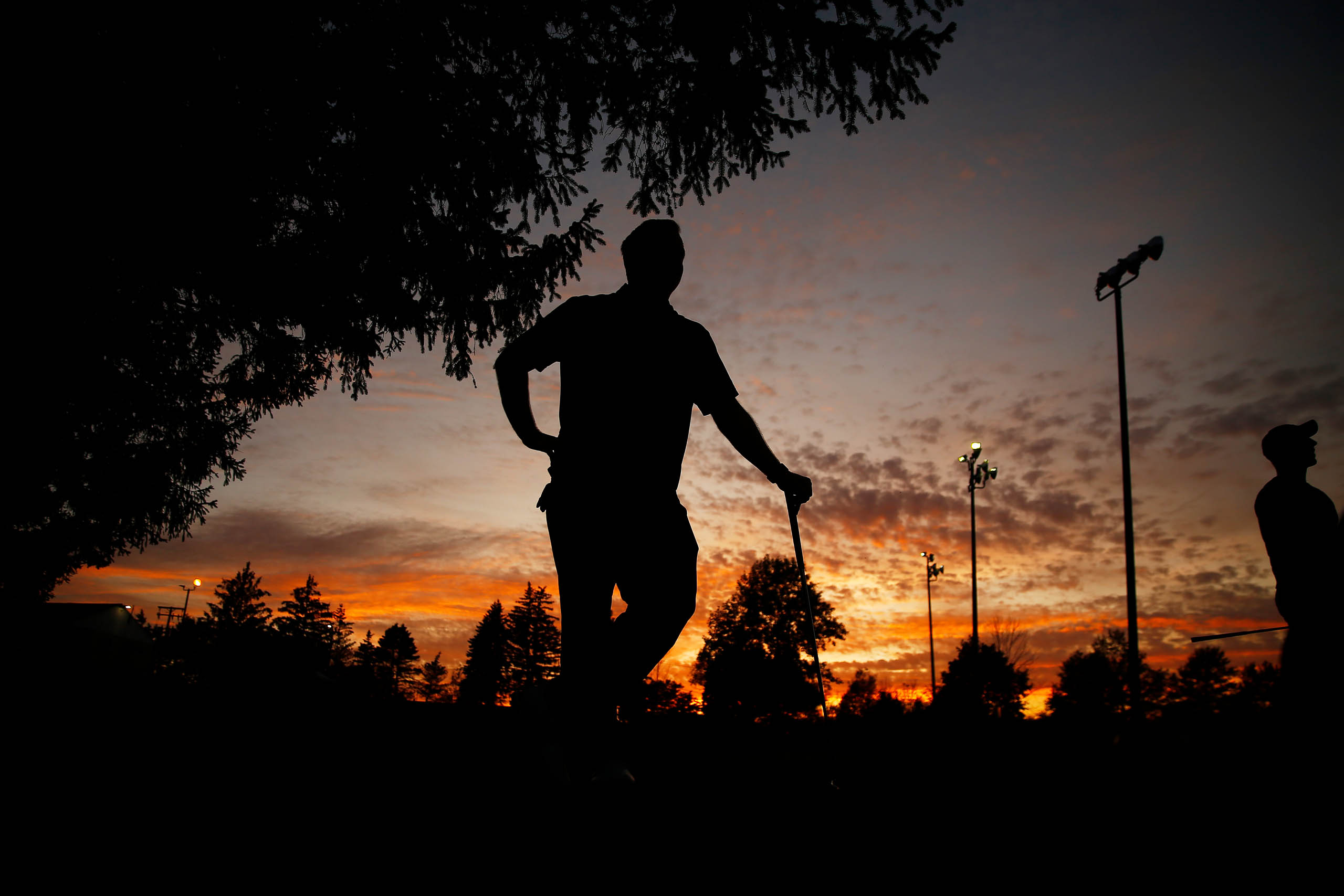 Chris Smith is silhouetted against the sunset before teeing off for night golf at the Bob-O-Link golf course on Friday September 20, 2019 in Orchard Park, New York. (Photo by Jared Wickerham/Golfers Journal)