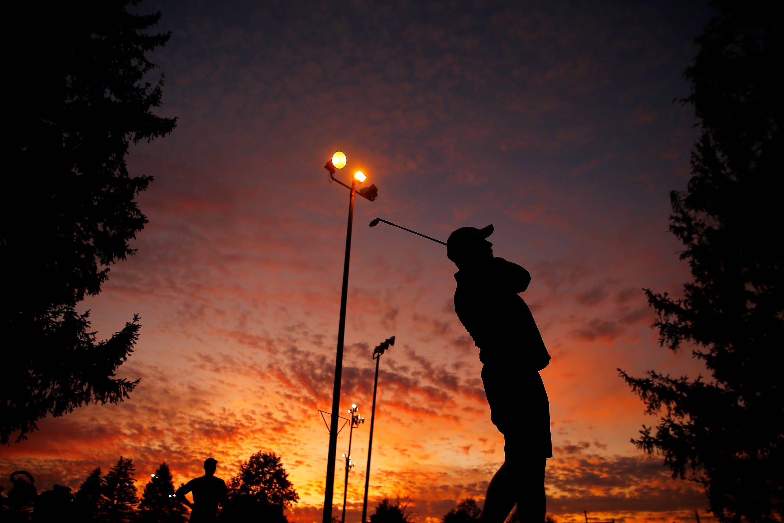 Ryan Donnelly is silhouetted against the sunset before teeing off for night golf at the Bob-O-Link golf course on Friday September 20, 2019 in Orchard Park, New York. (Photo by Jared Wickerham/Golfers Journal)