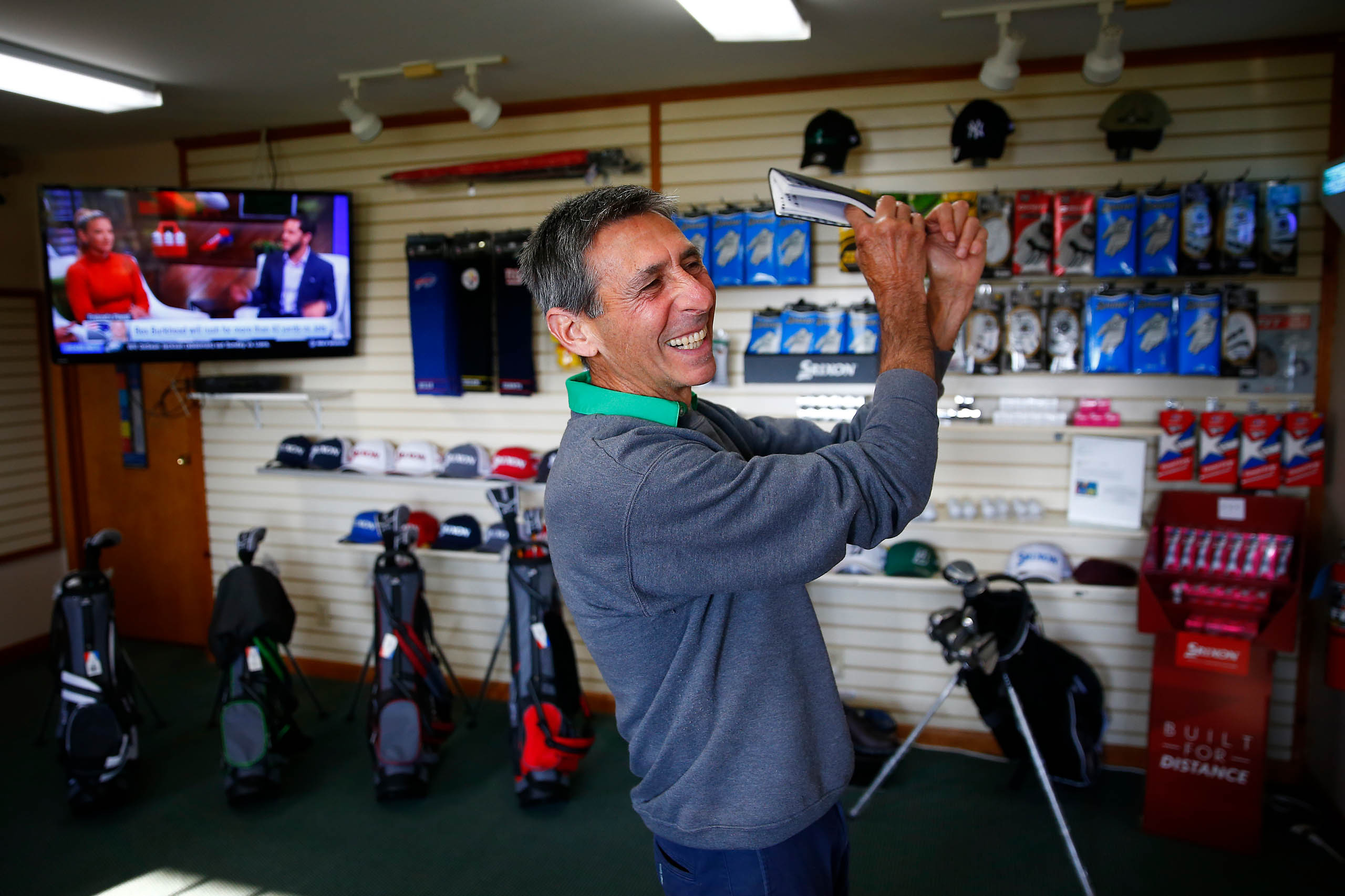 Jimmy Dref, golf pro at the Bob-O-Link golf course, pretends to swing while in conversation in the clubhouse. Photo by Jared Wickerham/Golfers Journal)
