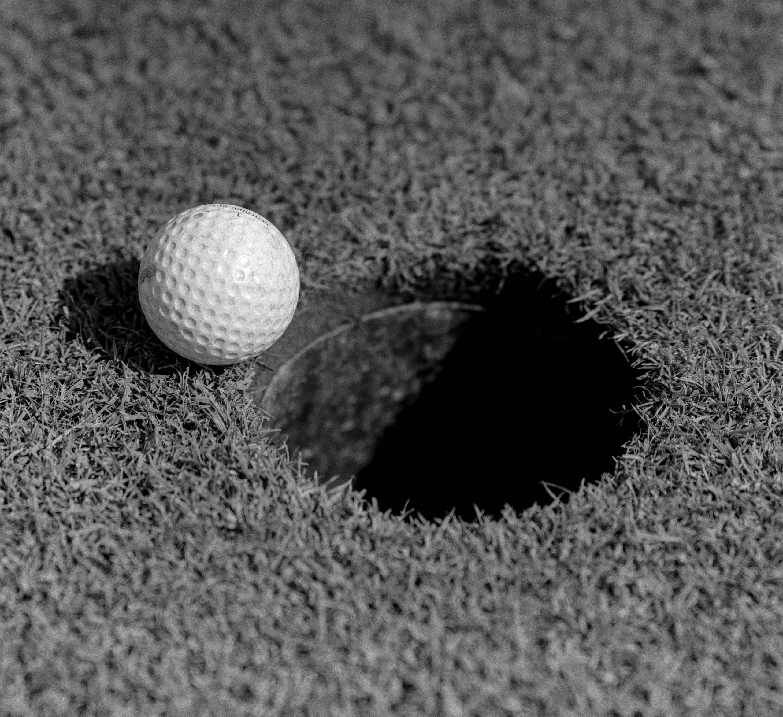 1950s CLOSE-UP OF GOLF BALL ON GREEN ON VERY EDGE OF CUP (Photo by H. Armstrong Roberts/ClassicStock/Getty Images)